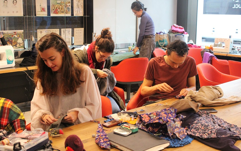 Students sewing on buttons and fixing holes in trousers