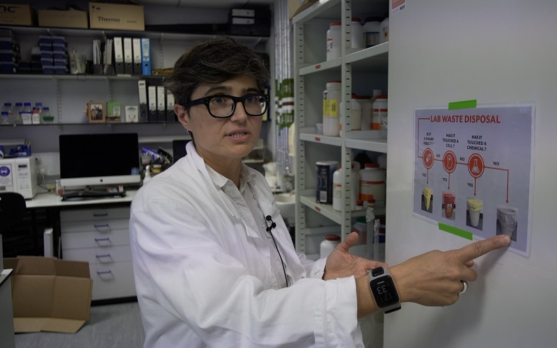 Researcher in a lab pointing at a sign