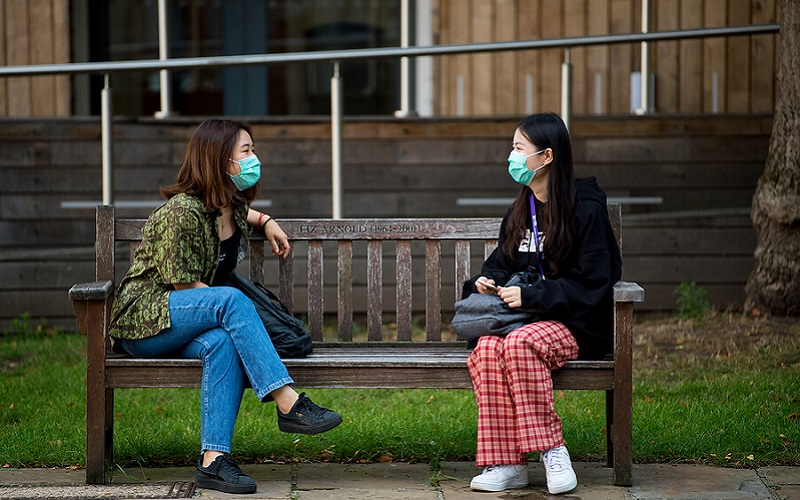 Two students wearing masks chatting on a park bench