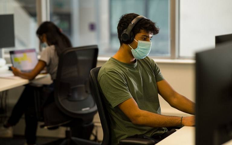 Students with masks studying at PCs