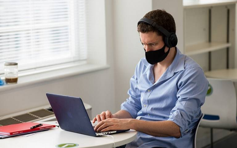 Man with mask and headphones typing on laptop