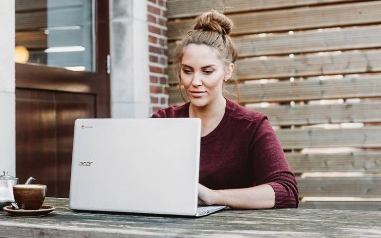 Student on laptop at a bench with a coffee. Credit: Anete Lusina/Unsplash.com