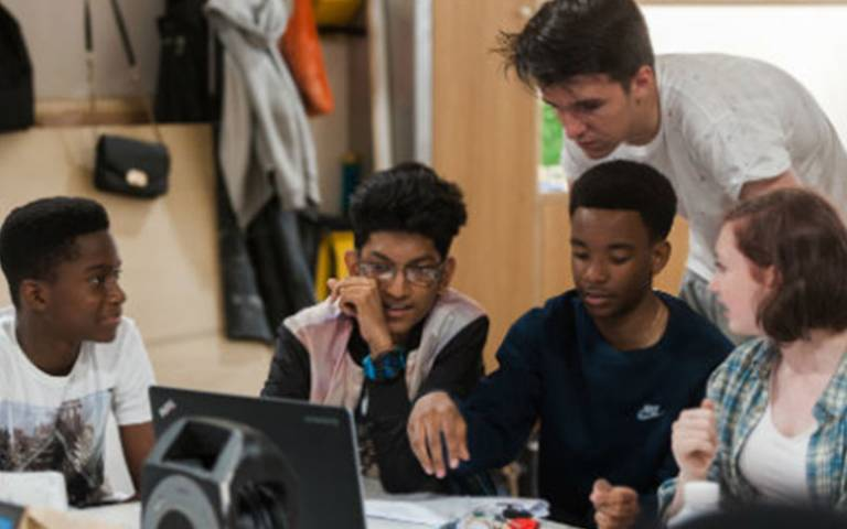 students working together around a computer