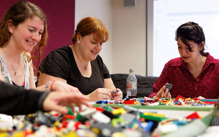 three students playing with lego and smiling