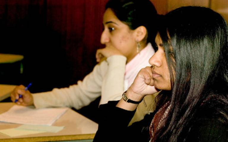 Two female students sitting in a classroom listening