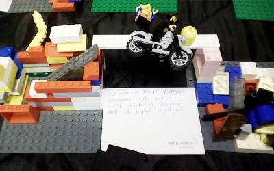 two lego models with a lego figure on a motorbike jumping in between