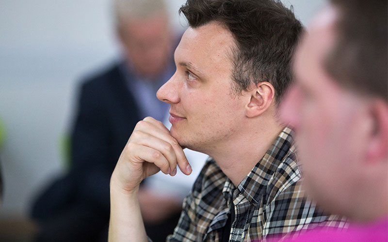 A member of staff listening to a presentation in a workshop