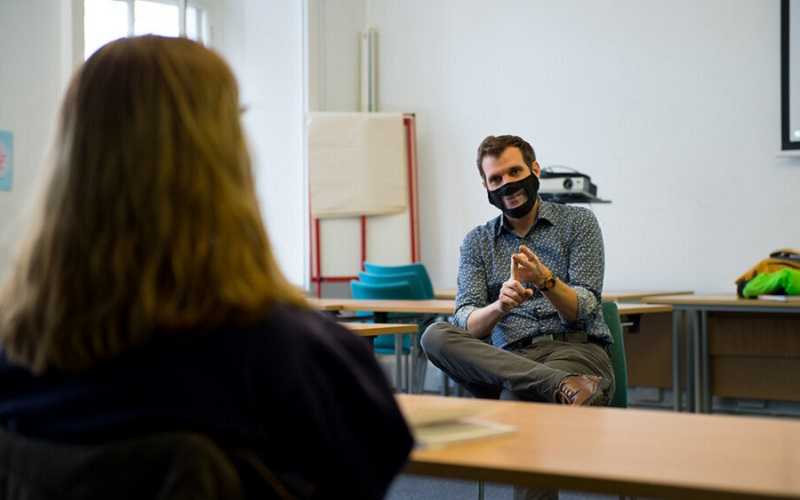 Teacher in mask in discussion with a student