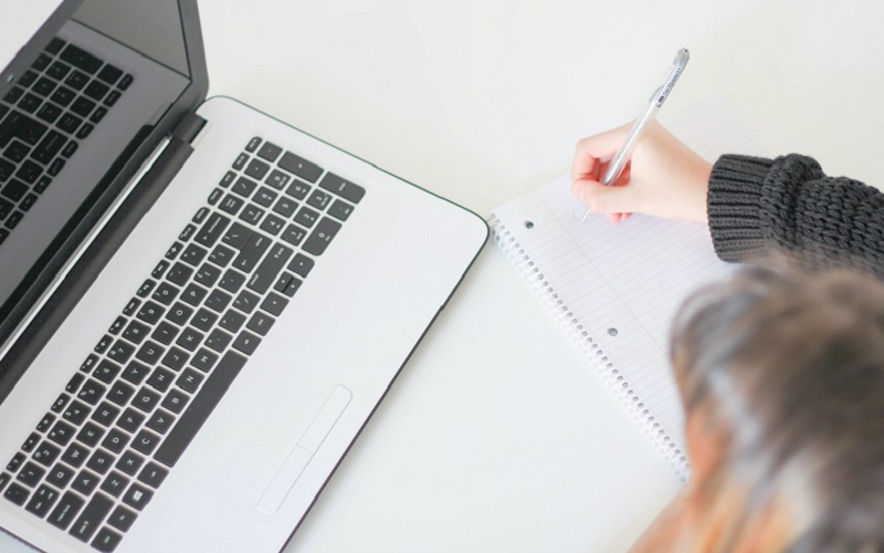Student taking notes in front of a laptop. Image credit: J Kelly Brito / Unsplash