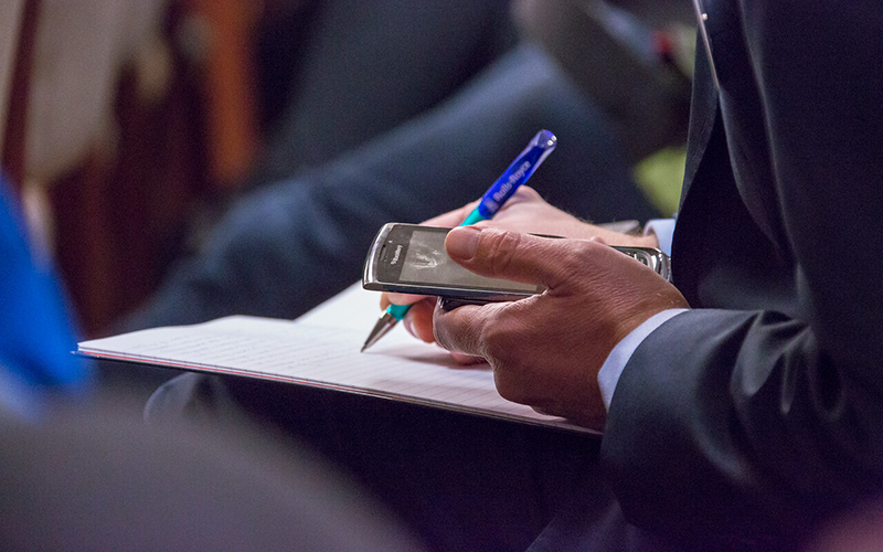 Image of man taking notes with phone in hand