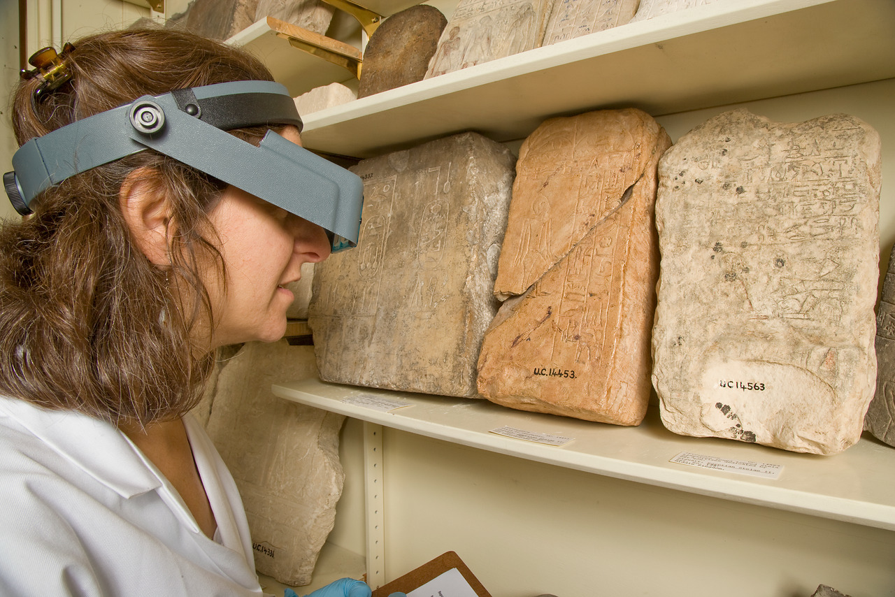 Researcher studying tablets in the Petrie Museum of Egyptology