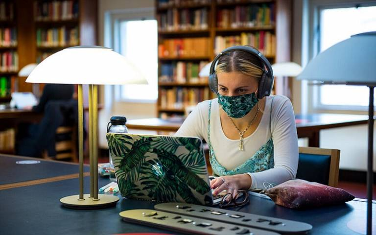 Student on laptop wearing headphones and mask