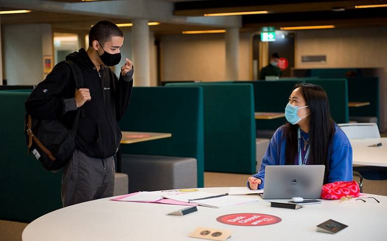 Two students in masks chatting