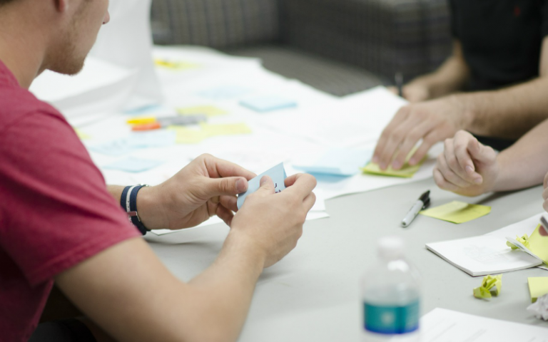 Photo of people using post its at a brainstorming session