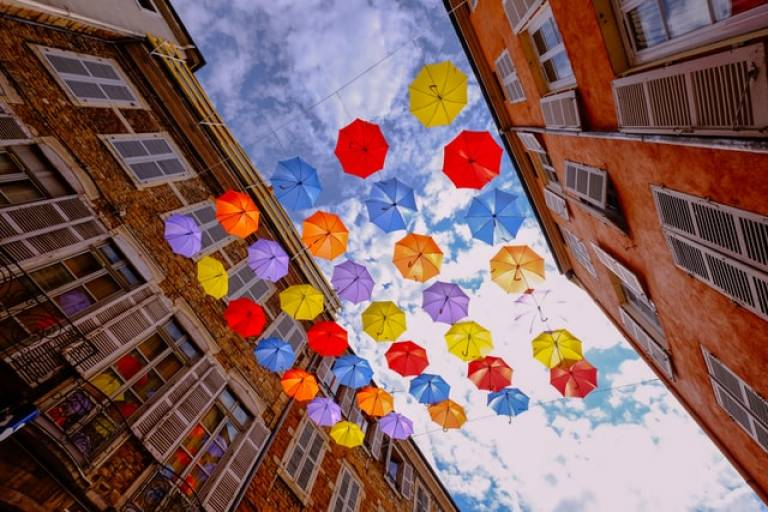 Photo of colourful umbrellas suspended in the middle of a street