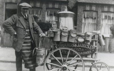 Old picture of man delivering milk on a cart.