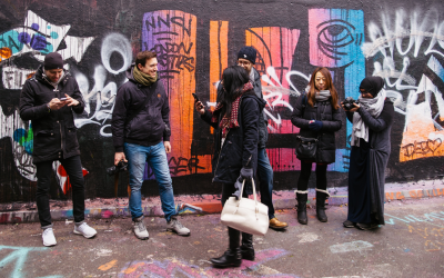People stand in front of a graffiti wall talking and laughing.
