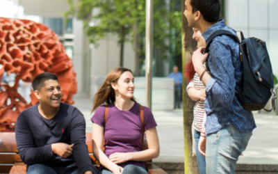 Summer school students talking around a bench.