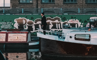 Person standing on a narrow boat on an East London canal.