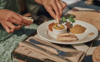 Person eating a plate of tapas style food.