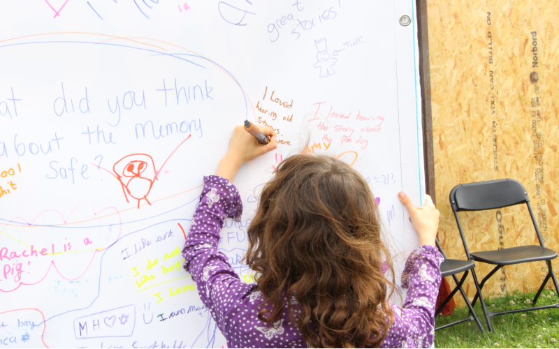 Girl writing on board at the Great Get Together 2019 event on QEOP