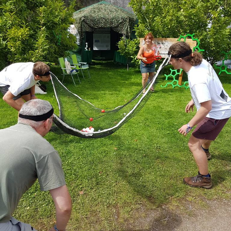 Festival goers play engagement game and catch balls with a head net