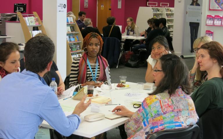 People talk around a desk during a workshop.