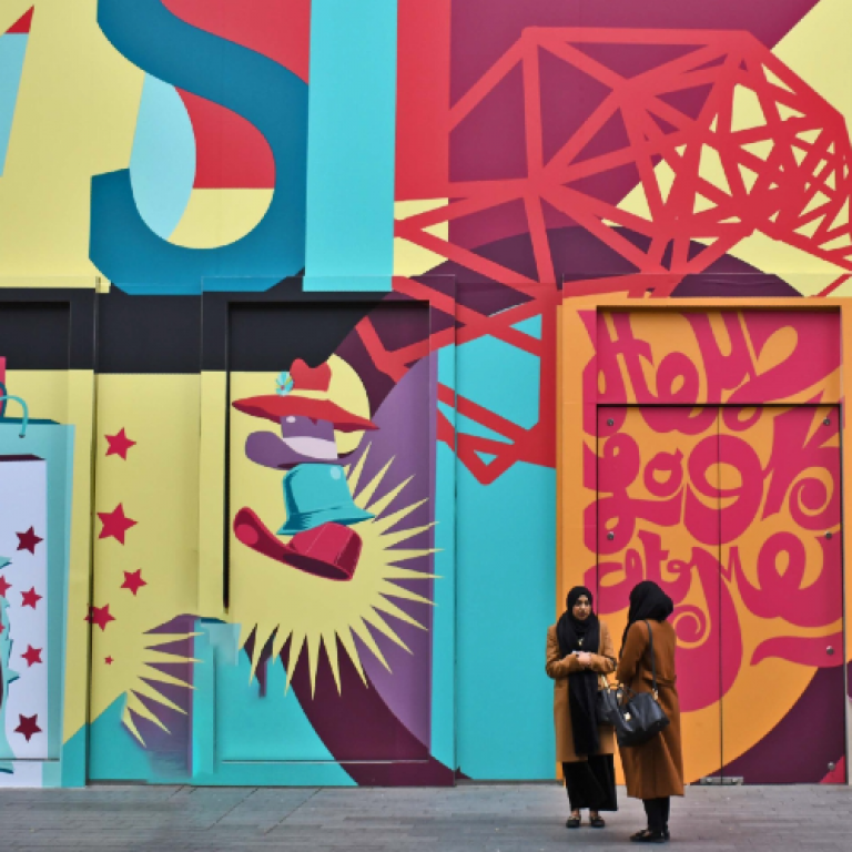 Two people stand in front of a colourful painted exterior wall.