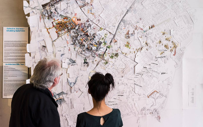 Two visitors look at an exhibition, a map, at The Bartlett summer showcase 2018.