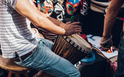 Musician sits playing a Djembe drum in a crowd of people.