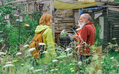 Two people stand in a floral garden.