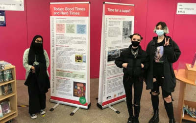 Three people stand in front of a display from Newham News Curators.