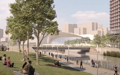 Architectural render of UCL East campus with people sat on grass verge on the side of a river.