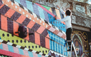 Artist working on a graffiti wall.