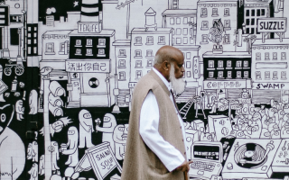 Man walking past a cartoon mural wall.
