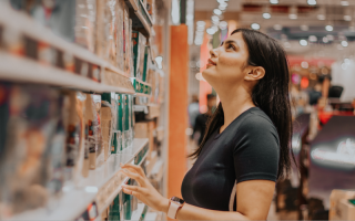 Woman looking at products on shop shelf.