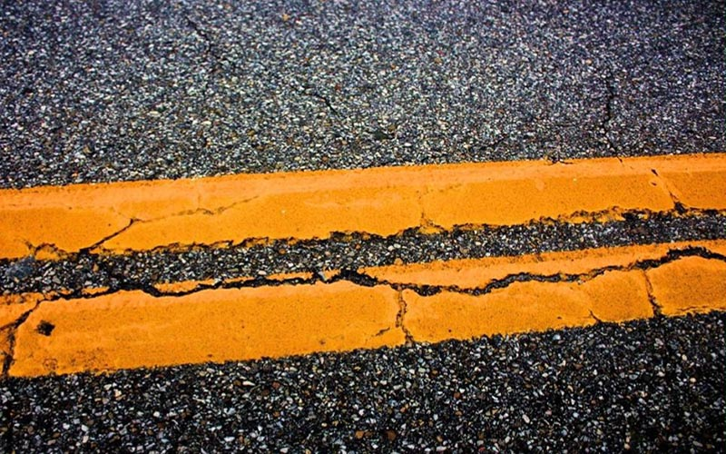 Image of cracked orange parking restriction markings on a road