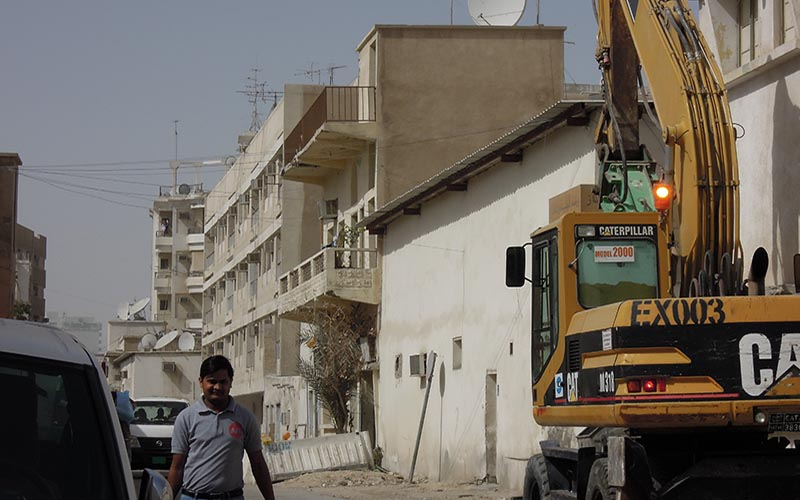 A man walks down a street in Doha next to a construction vehicle