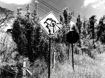 Surveillance camera graffiti on road sign