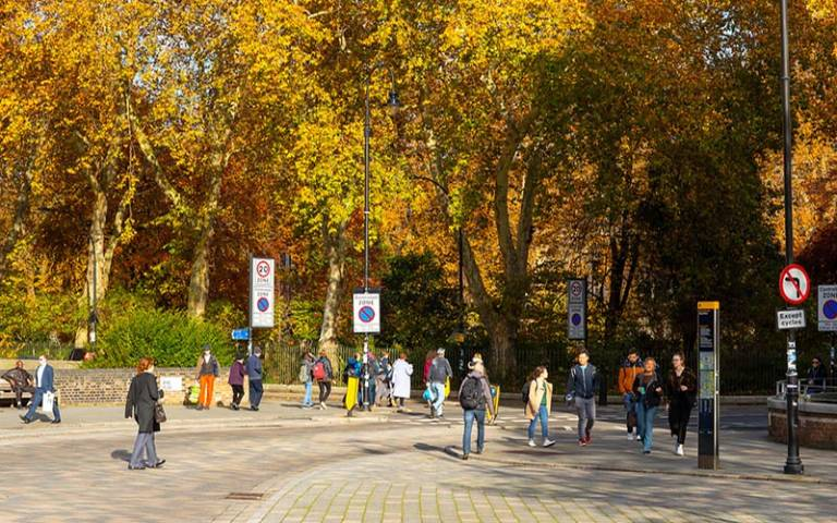 People walking on Byng Place. An Autumnal Gordon Square gardens is in the Background. © UCL Digital Media