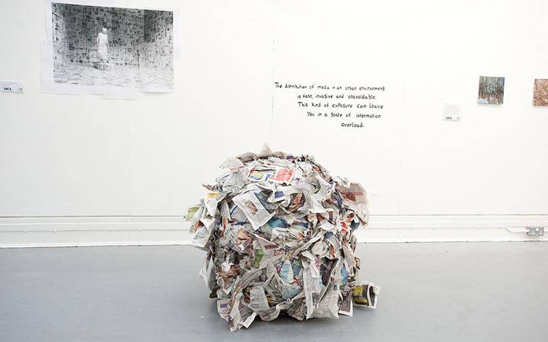 An oversized crumpled up ball of newspapers sits on a gallery floor