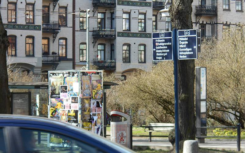 Street scene in Gothenburg with a car passing and posters stuck to a piece of street furniture