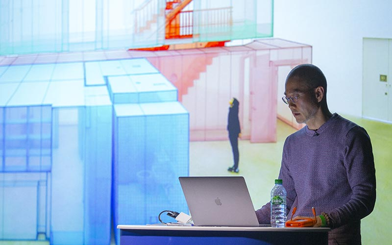 Do Ho Suh standing at a lecturn with a presentation screen behind him