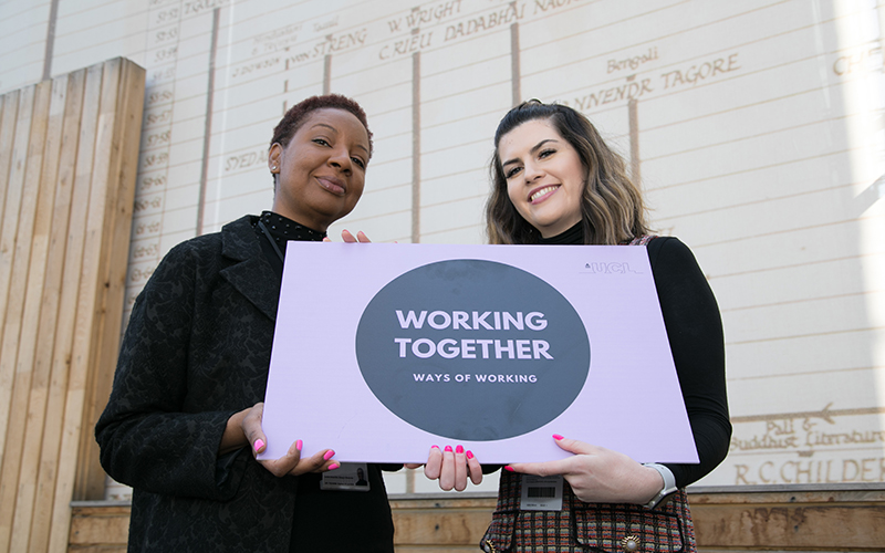 Two members of staff holding up a ways of working - working together sign