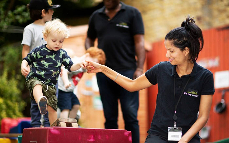 Nursery staff holding the hand of a young child